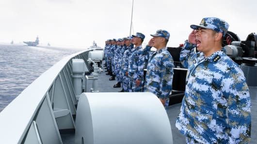A PLA Navy fleet including the aircraft carrier Liaoning, submarines, vessels and fighter jets take part in a review in the South China Sea last April.