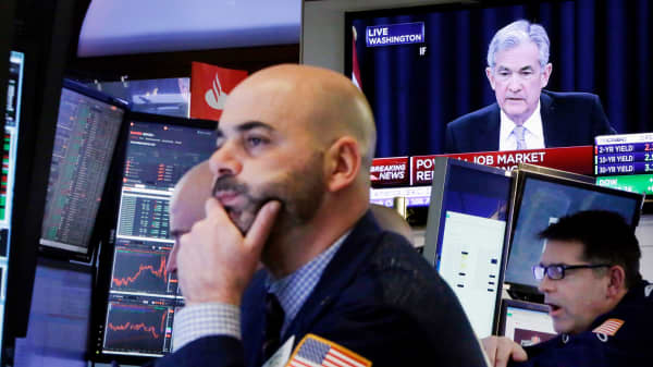 Federal Reserve Chairman Jerome Powell appears on a television on the floor of the New York Stock Exchange.