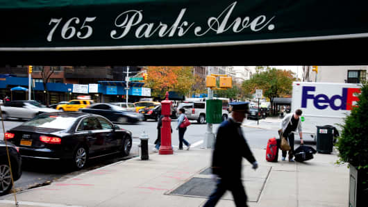 A doorman walks under an awning of a residential building on Park Avenue in New York.