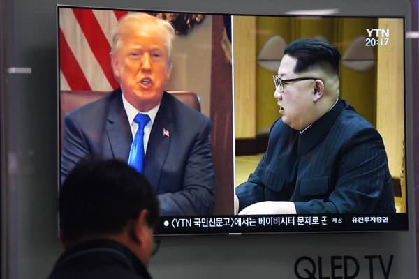 A man watches a television news showing North Korean leader Kim Jong Un (R) and US President Donald Trump (L), at a railway station in Seoul on May 24, 2018.