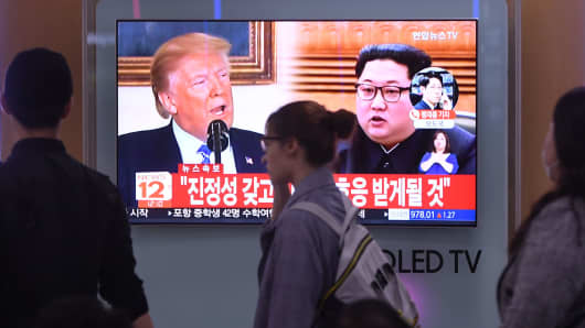 People walk past a television news screen showing North Korean leader Kim Jong Un (R) and US President Donald Trump (L) at a railway station in Seoul on May 16, 2018.