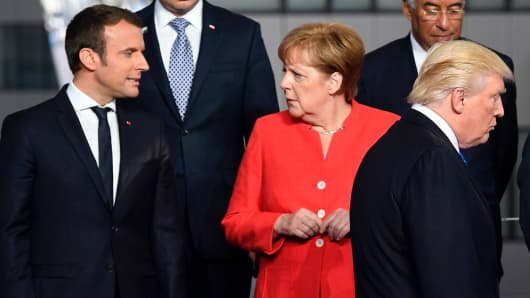French President Emmanuel Macron (L) and German Chancellor Angela Merkel (2nd L) speaks as US President Donald Trump (C) arrives for a family picture during the NATO (North Atlantic Treaty Organization) summit at the NATO headquarters, in Brussels, on May 25, 2017.