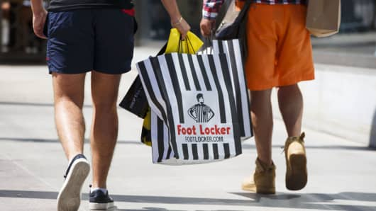 Customers walk with Foot Locker shopping bags on the Third Street Promenade in Santa Monica, California.