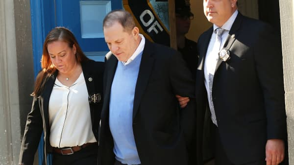 Harvey Weinstein is led out of the New York Police Department's First Precinct in handcuffs after being arrested and processed on charges of rape, committing