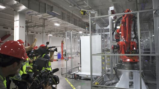 Members of the media film machinery inside the Tesla Gigafactory in Sparks, Nevada.