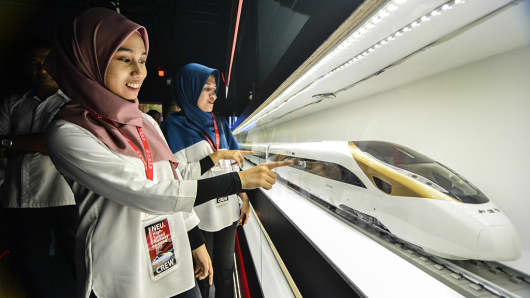 Visitors look at a model of a bullet train designed by China at an exhibition on high-speed rail in Kuala Lumpur, Malaysia, on Jan. 16, 2017.