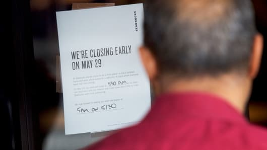 "A man reads a notice stating ""We're Closing Early On May 29,"" posted outside a Starbucks store, before more than 8,000 branches nationwide will close this afternoon for anti-bias training, in Philadelphia, May 29, 2018."