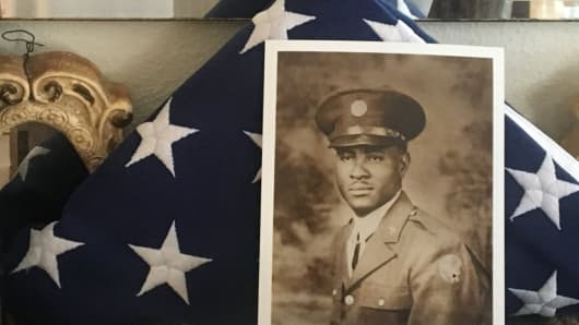 A photograph of Richard Overton in his military uniform is propped up against a folded American flag in his home.