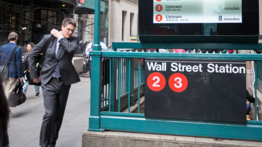 Pedestrians walk past an entrance to the Wall Street subway station near the New York Stock Exchange.