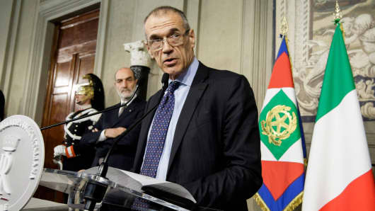 Italy's designated Prime Minister Carlo Cottarelli talks to journalists after having received from Italy's President Sergio Mattarella the mandate to form a new government at the Quirinale Palace, May 29, 2018.