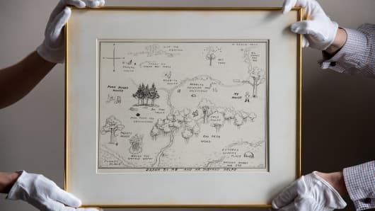Sotheby's art handlers hold 'The Original Map of the Hundred Acre Wood' by E.H. Shepard.