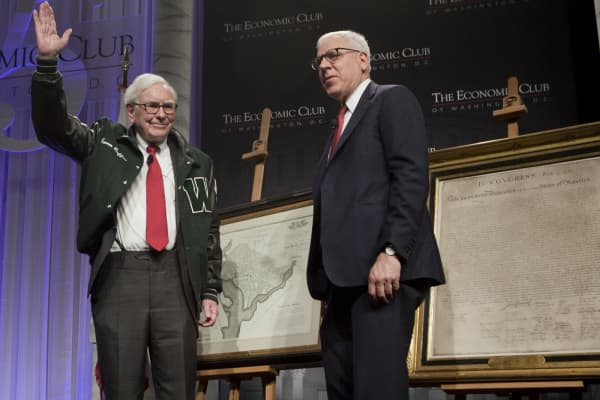 Warren Buffett, left, waves after receiving a Woodrow Wilson High School jacket from David Rubenstein during the Economic Club of Washington dinner event in Washington, D.C., U.S., on Tuesday, June 5, 2012.