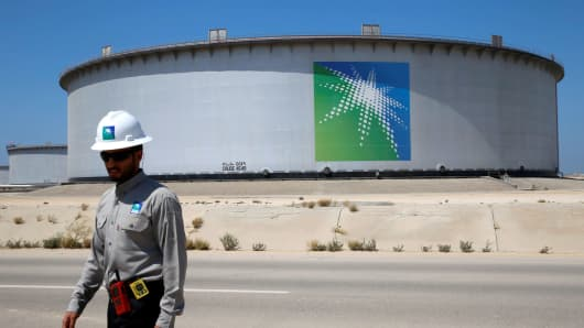 An Aramco employee walks near an oil tank at Saudi Aramco's Ras Tanura oil refinery and oil terminal in Saudi Arabia.