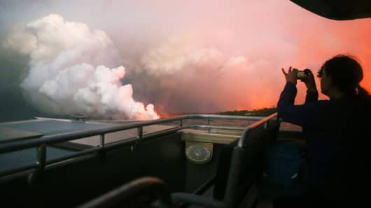 A woman takes photos while riding a tour boat to view Kilauea volcano lava entering the Pacific Ocean at dawn, as a steam plume rises, on Hawaii's Big Island on May 22, 2018 near Pahoa, Hawaii.