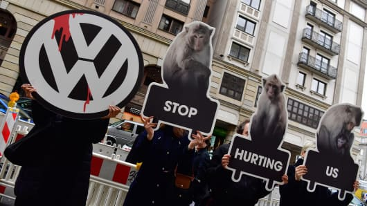 Protesters hold up posters with the logo of Volkswagen (VW) and of monkeys as they protest against animal testing in front of VW's showrooom, the venue where the German car maker is holding its annual press conference, in Berlin on March 13, 2018.