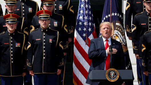 "President Donald Trump holds his hand over his heart and sings the U.S. National Anthem along with members of the U.S. military at the ""celebration of America"" event on the South Lawn of the White House in Washington, June 5, 2018."