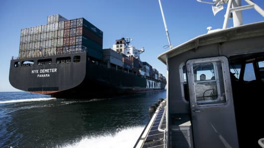 A boat pulls alongside the NYK Demeter container ship outside the Port of Los Angeles.