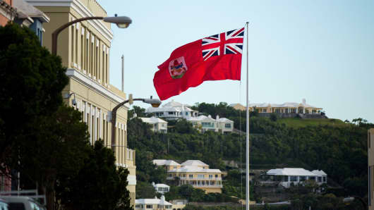The flag of Bermuda flies as houses dot the hillside across Hamilton Harbour, in Hamilton, Bermuda.