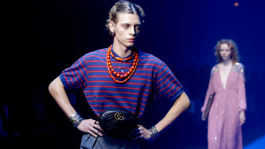 A model wears a creation part of Gucci's women Fall/Winter 2018/19 fashion collection, presented in Milan, Italy, Wednesday, Sept. 20, 2017. Casual luxury is driving global sales, forecast to grow 6 percent this year, as high-end consumers look for low-brow statements in T-shirts, sneakers and rubber sliders, according to a new study by consultancy Bain released Thursday, June 7, 2018.