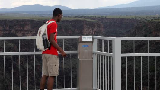 A tourist stops to read the message on the crisis hotline situated on the The Rio Grande Gorge Bridge.