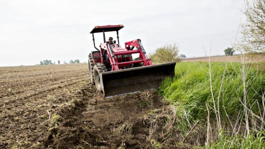 A tractor fills in an area of a corn field where rains washed out the soil in Princeton, Illinois.