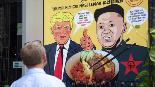 A man looks at a promotional poster outside a local eatery, Harmony Nasi Lemak, which offers a special Trump Kim-Chi dish to its menu on June 6, 2018 in Singapore.