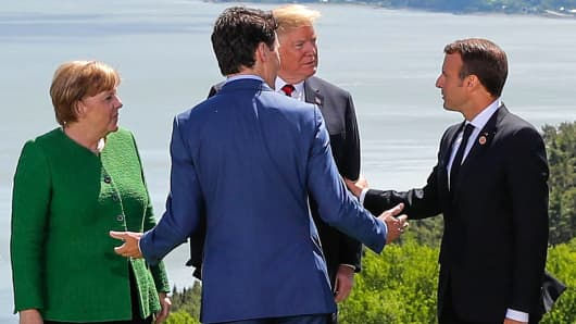 Germany's Chancellor Angela Merkel, U.S. President Donald Trump, Canada's Prime Minister Justin Trudeau and France's President Emmanuel Macron chat during a family photo at the G7 Summit in the Charlevoix city of La Malbaie, Quebec, Canada, June 8, 2018.