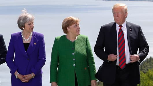 Britain's Prime Minister Theresa May, Germany's Chancellor Angela Merkel and U.S. President Donald Trump pose during a family photo at the G7 Summit in the Charlevoix city of La Malbaie, Quebec, Canada, June 8, 2018.