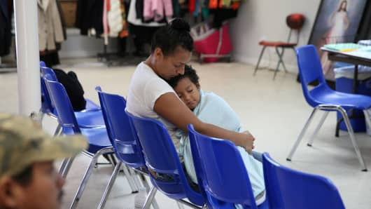 "An undocumented Honduran immigrant and her son, recently released from detention through ""catch and release"" immigration policy, pass time at the Catholic Charities relief center in McAllen, Texas, U.S., April 14, 2018."