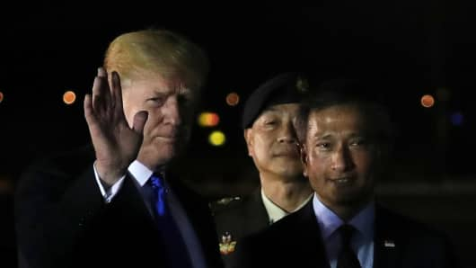 President Donald Trump waves next to Singapore's Foreign Minister Vivian Balakrishnan after arriving in Singapore June 10, 2018.