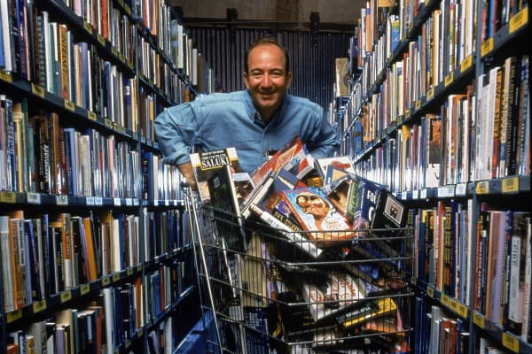 Portrait of American businessman and Amazon.com CEO Jeff Bezos poses in an aisle of bookshelves with a shopping cart full of books and compact discs, Seattle, Washington, September 1998.