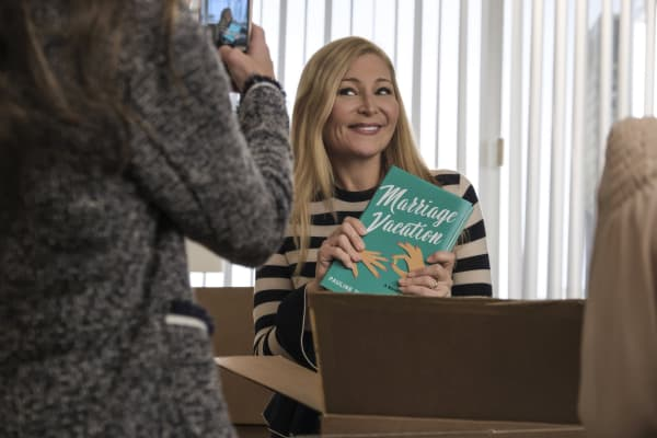 "Pauline Turner Brooks (played by Jennifer Westfeldt) holding up a copy of her novel, ""Marriage Vacation,"" on the TV Land series ""Younger."" ""Marriage Vacation"" is now a book in real life too."