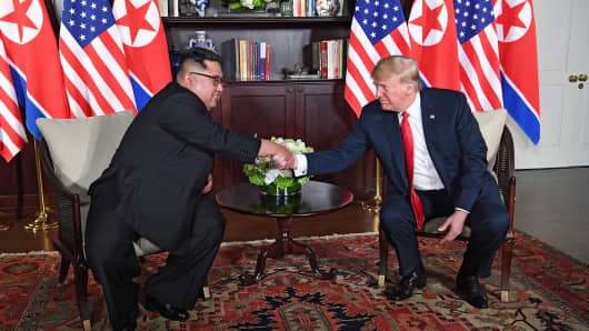 President Donald Trump (R) shakes hands with North Korea's leader Kim Jong Un (L) as they sit down for their historic US-North Korea summit, at the Capella Hotel on Sentosa island in Singapore on June 12, 2018.