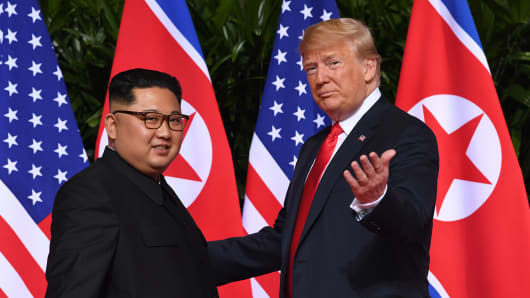 President Donald Trump (R) gestures as he meets with North Korea's leader Kim Jong Un (L) at the start of their historic US-North Korea summit, at the Capella Hotel on Sentosa island in Singapore on June 12, 2018.