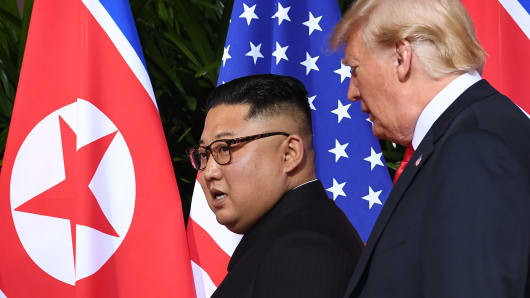 President Donald Trump (R) walks with North Korea's leader Kim Jong Un (L) at the start of their historic US-North Korea summit, at the Capella Hotel on Sentosa island in Singapore on June 12, 2018.