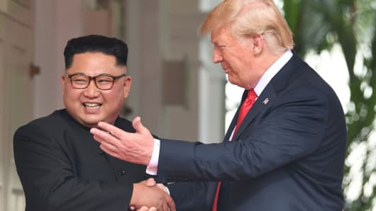 President Donald Trump (R) shakes hands with North Korea's leader Kim Jong Un as they meet at the start of their historic US-North Korea summit, at the Capella Hotel on Sentosa island in Singapore on June 12, 2018.
