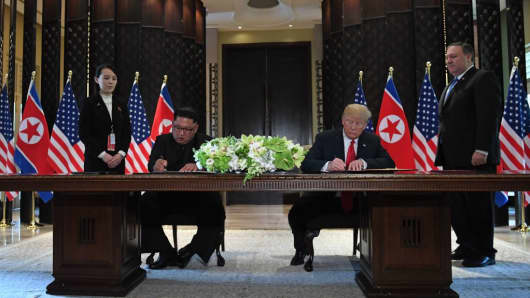 US President Donald Trump (2nd R) and North Korea's leader Kim Jong Un (2nd L) sign documents as US Secretary of State Mike Pompeo (R) and the North Korean leader's sister Kim Yo Jong (L) look on at a signing ceremony during their historic US-North Korea summit, at the Capella Hotel on Sentosa island in Singapore on June 12, 2018.