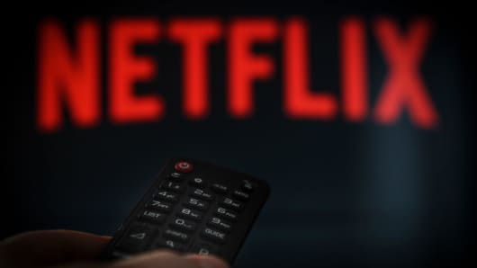 A remote control is seen being held in front of a television running the Netflix application