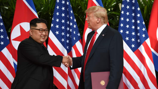 U.S. President Donald Trump and North Korea's leader Kim Jong Un shake hands during their summit at the Capella Hotel on Sentosa island in Singapore June 12, 2018.
