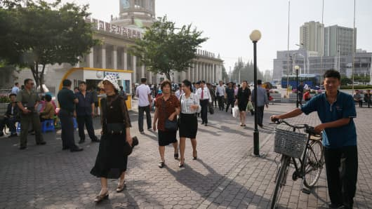 People walk through a public square outside the central railway station in Pyongyang on June 12, 2018.