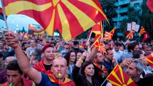 People wave Macedonian flags during a protest in front of the Government building in Skopje on June 2, 2018.
