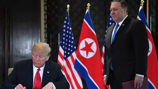 President Donald Trump (L) signs a document while US Secretary of State Mike Pompeo looks on during a signing ceremony with North Korea's leader Kim Jong Un during their historic US-North Korea summit, at the Capella Hotel on Sentosa island in Singapore on June 12, 2018.