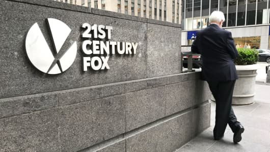 A man stands beside the 21st Century Fox sign outside their offices in New York.