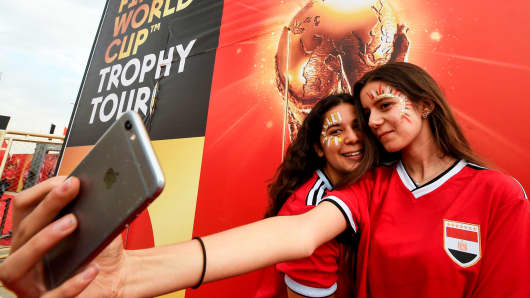 Female Egyptian football fans pose for a 'selfie' photograph taken with a cell phone during a FIFA World Cup Trophy tour event in the capital Cairo on March 15, 2018.
