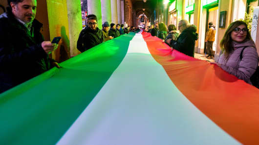 Members of a political party hold an Italian flag in Rome, Italy.
