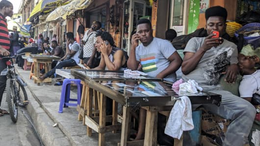 Street vendors selling mobile phone handsets wait for customers in Accra, Ghana, on March 15, 2018.