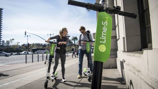 People use a smartphone to unlock LimeBike shared electric scooters on the Embarcadero in San Francisco.