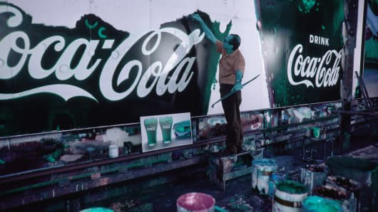 A graphic artist paints a Coca-Cola billboard.