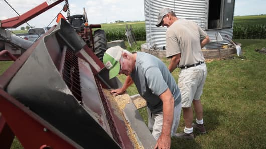 Farmer John Duffy (L) and Roger Murphy load soybeans from a grain bin onto a truck before taking them to a grain elevator on June 13, 2018 in Dwight, Illinois. U.S. soybean futures plunged with renewed fears that China could hit U.S. soybeans with retaliatory tariffs if the Trump administration follows through with threatened tariffs on Chinese goods.