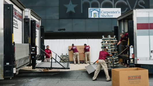 A team of movers work to load residents' belongings into the Carpenter's Shelter in an abandoned Macy's department store, at Landmark Mall in Alexandria, Va., June 9, 2018.